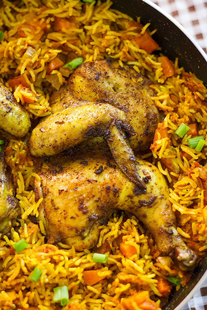 A skillet of yellow rice with vegetables and roasted chicken.