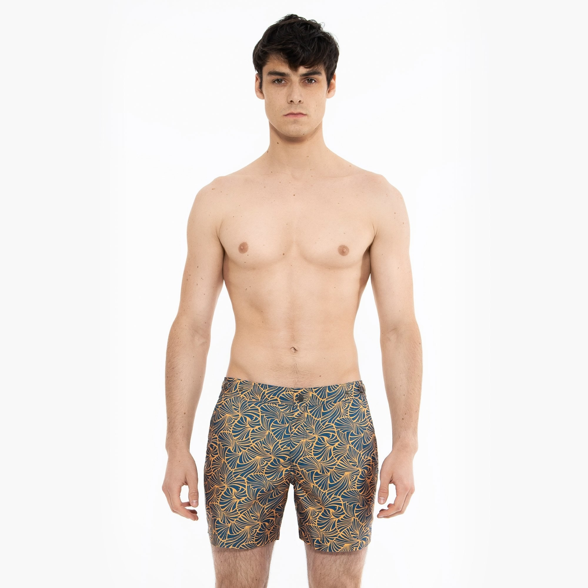 model wearing the mid-thigh length swim trunks with gold seashell print