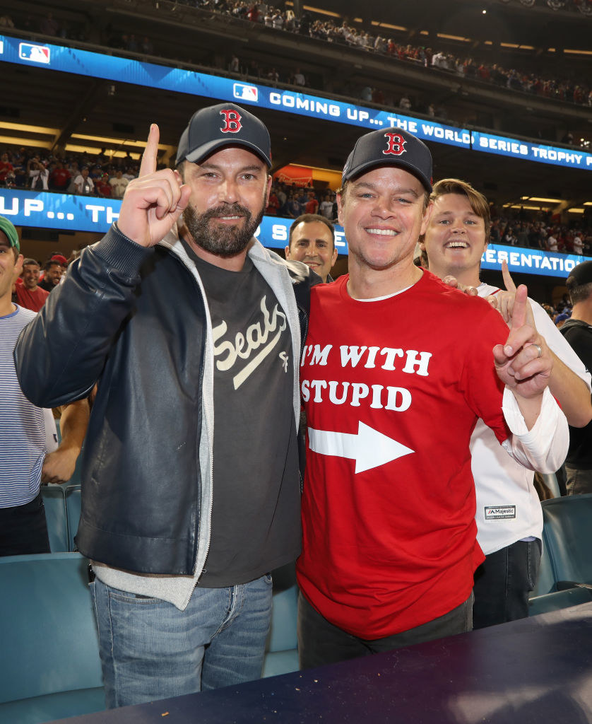 Ben Affleck and Matt Damon at a Boston Red Sox game holding up number one signs with their fingers in 2018