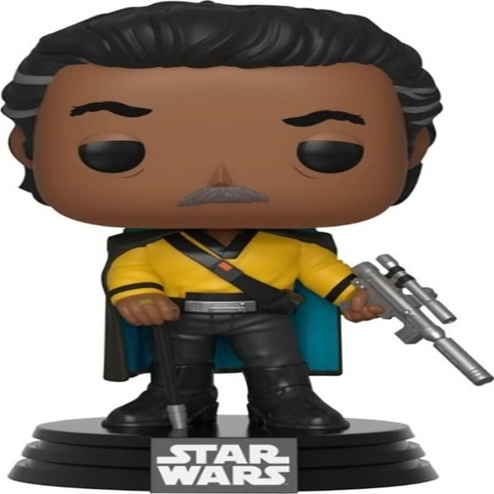 the older version of lando with gray streaked hair holding his weapon