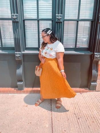 Reviewer wearing orange skirt