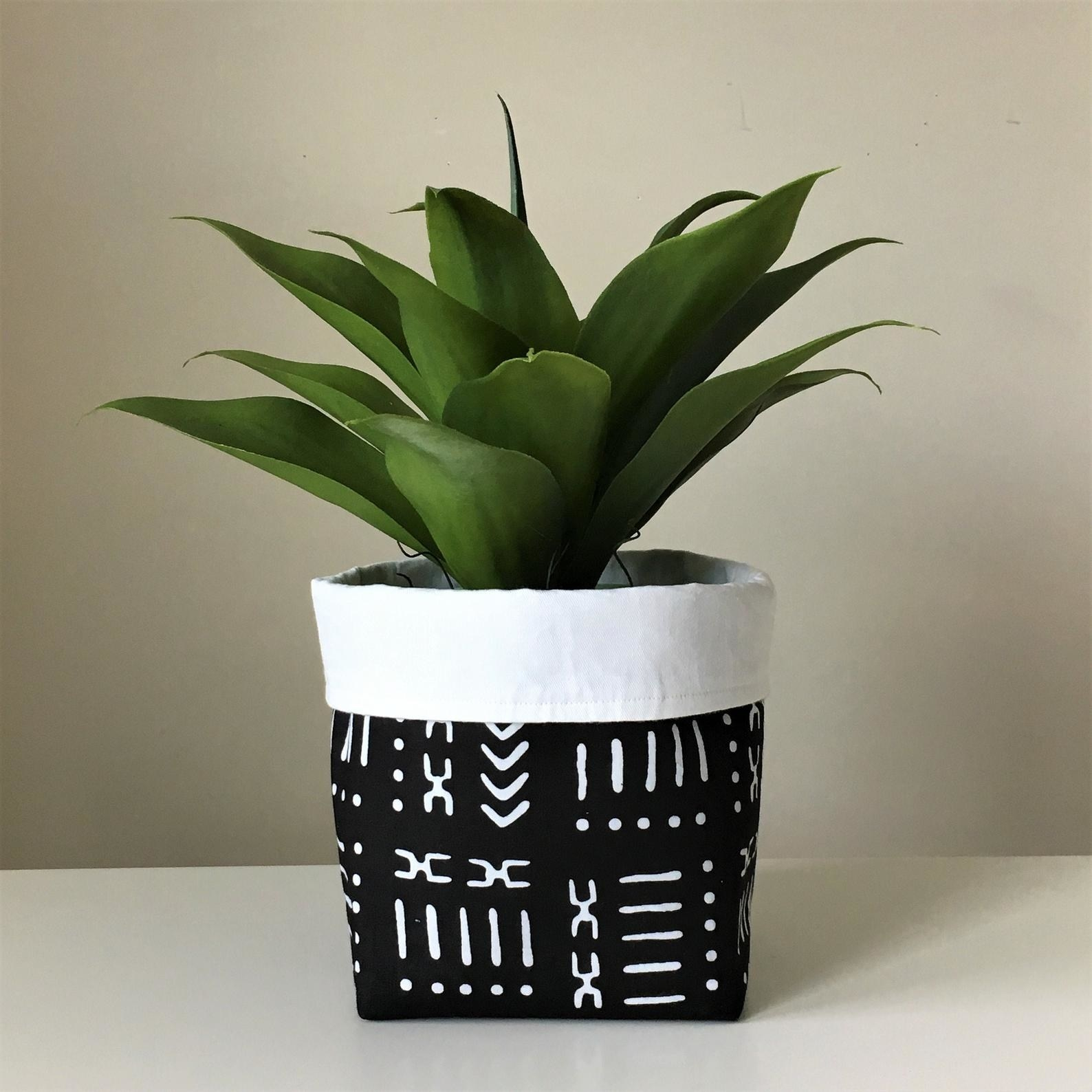 The fabric basket with a plant in it in black with white printed design all over it and the top part folded down to show the other wite side