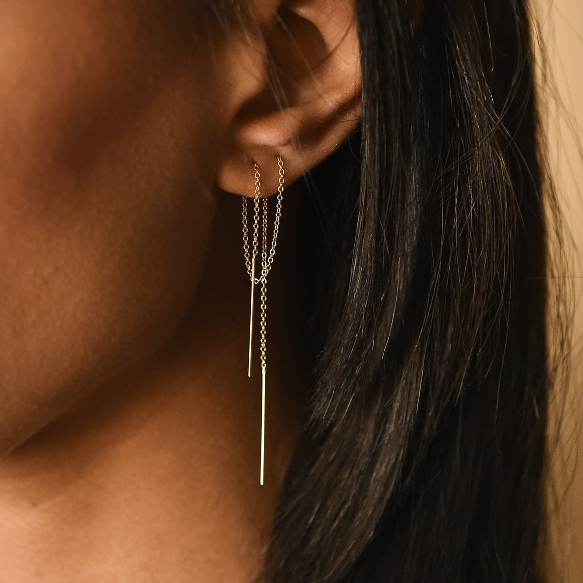 small gold chain thread earrings threaded through two piercings in an ear