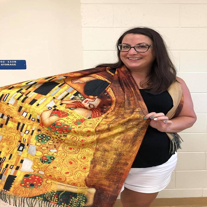 """Reviewer showing off the scarf printed with """"The Kiss"""" by Gustav Klimt"""