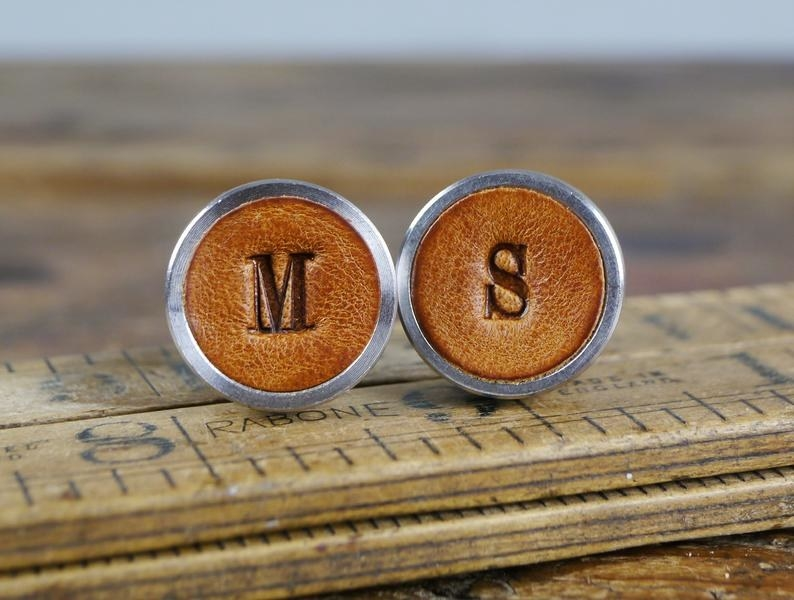 circular cuff links made of leather with the letters M and S on them