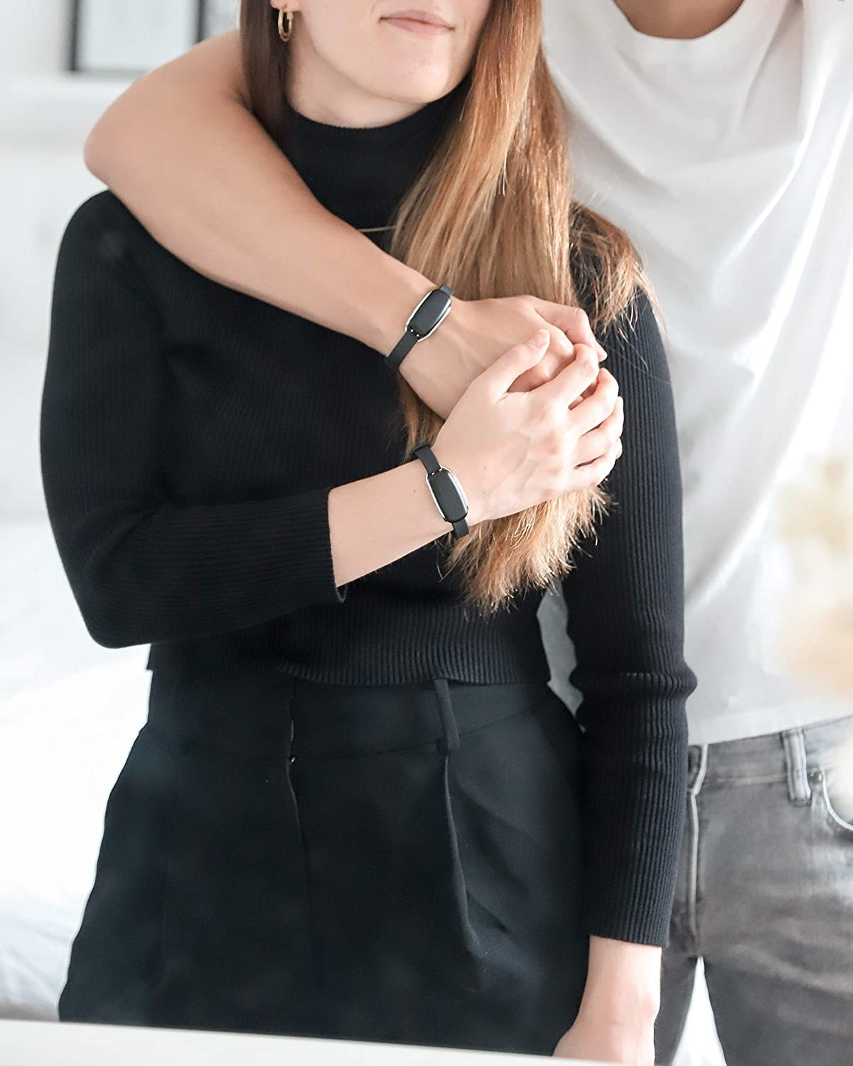 Two models holding hands and wearing the bracelets