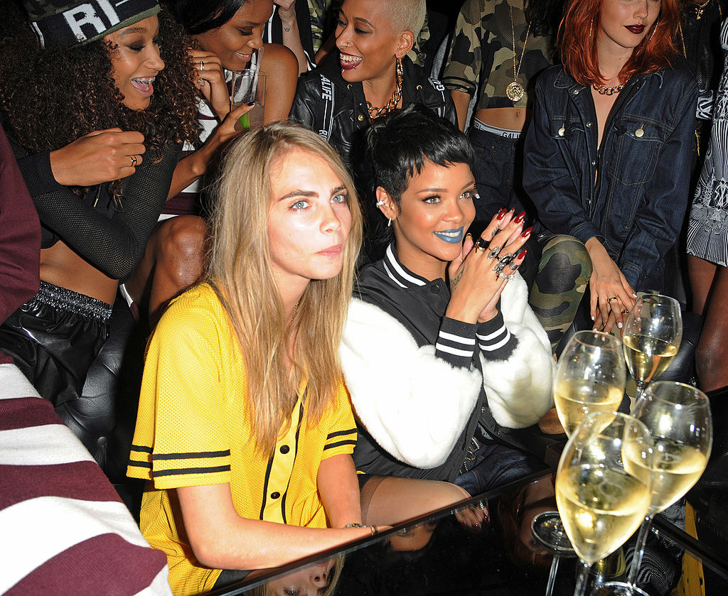 Cara Delevingne and Rihanna sitting together with wine glasses