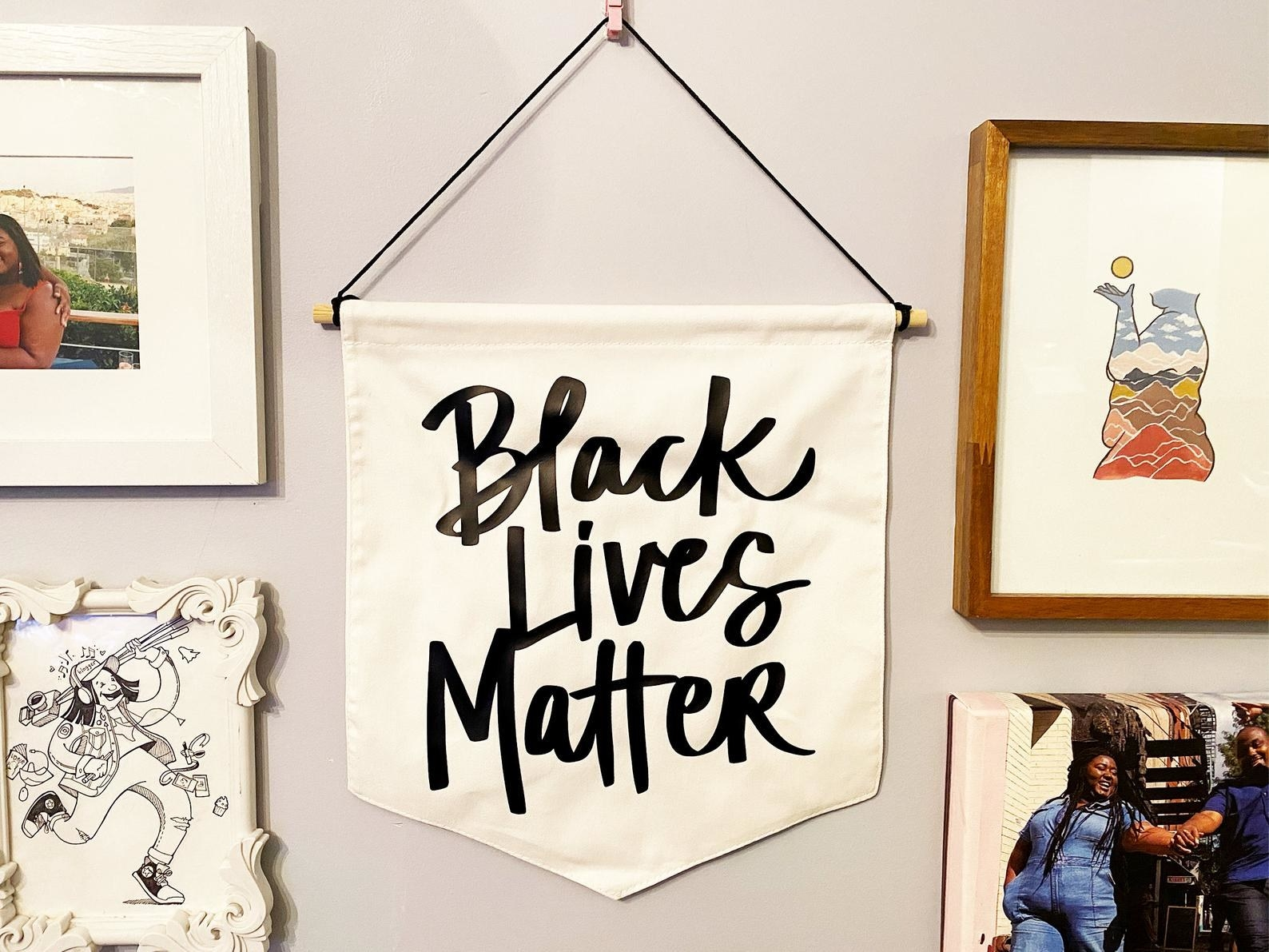 "white wall hanging with the words ""Black lives matter"" written in black"