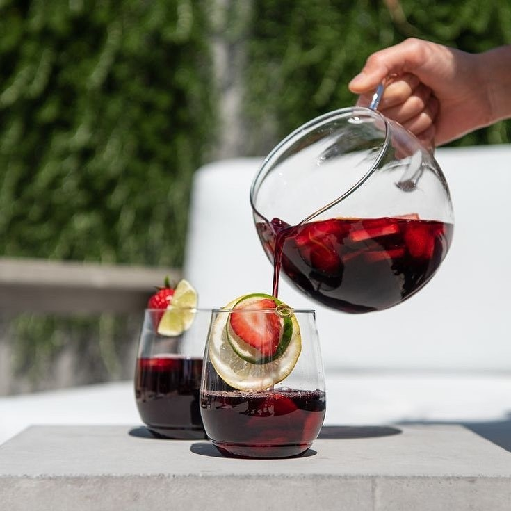 A person pouring sangria into a pair of stacking plastic wine glasses