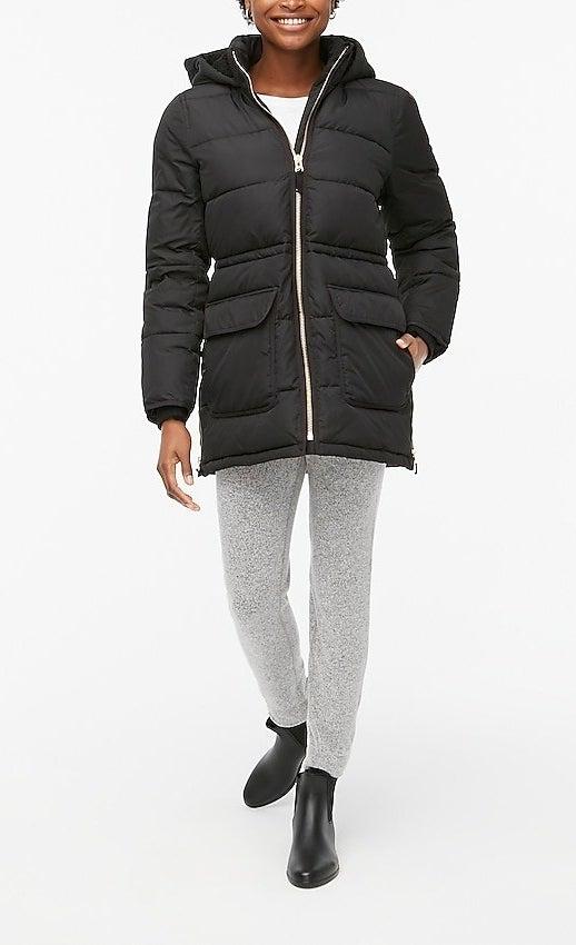 Model wearing black zip-up coat