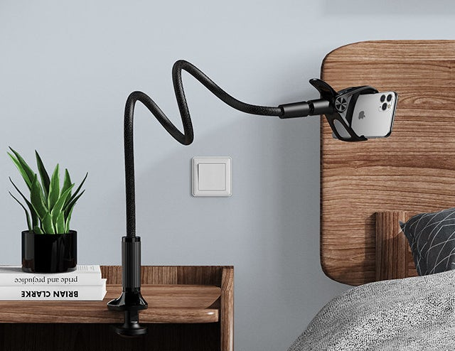 The flexible phone stand clipped onto a bedside table