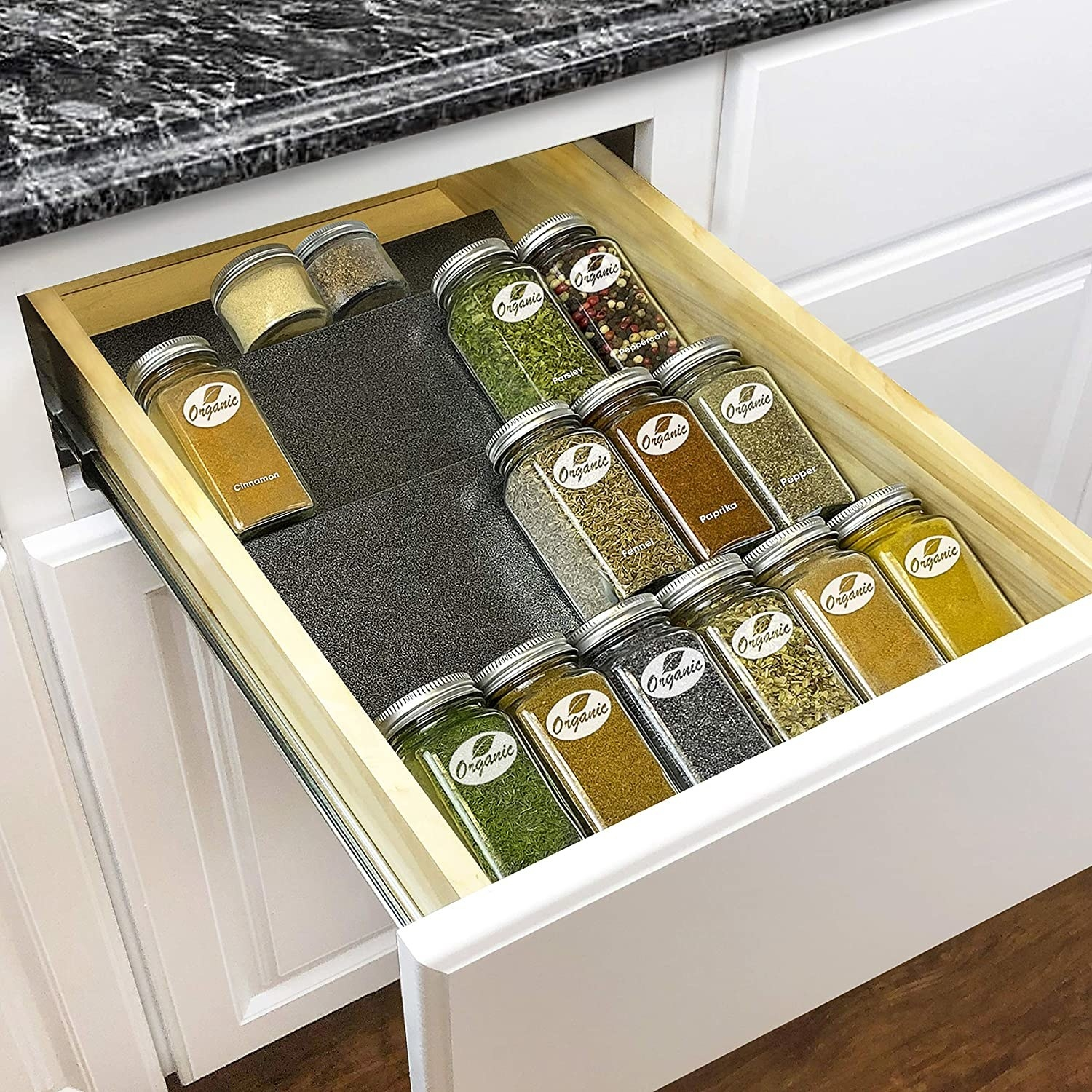 The spice rack tray in a drawer with an assortment of spices on it