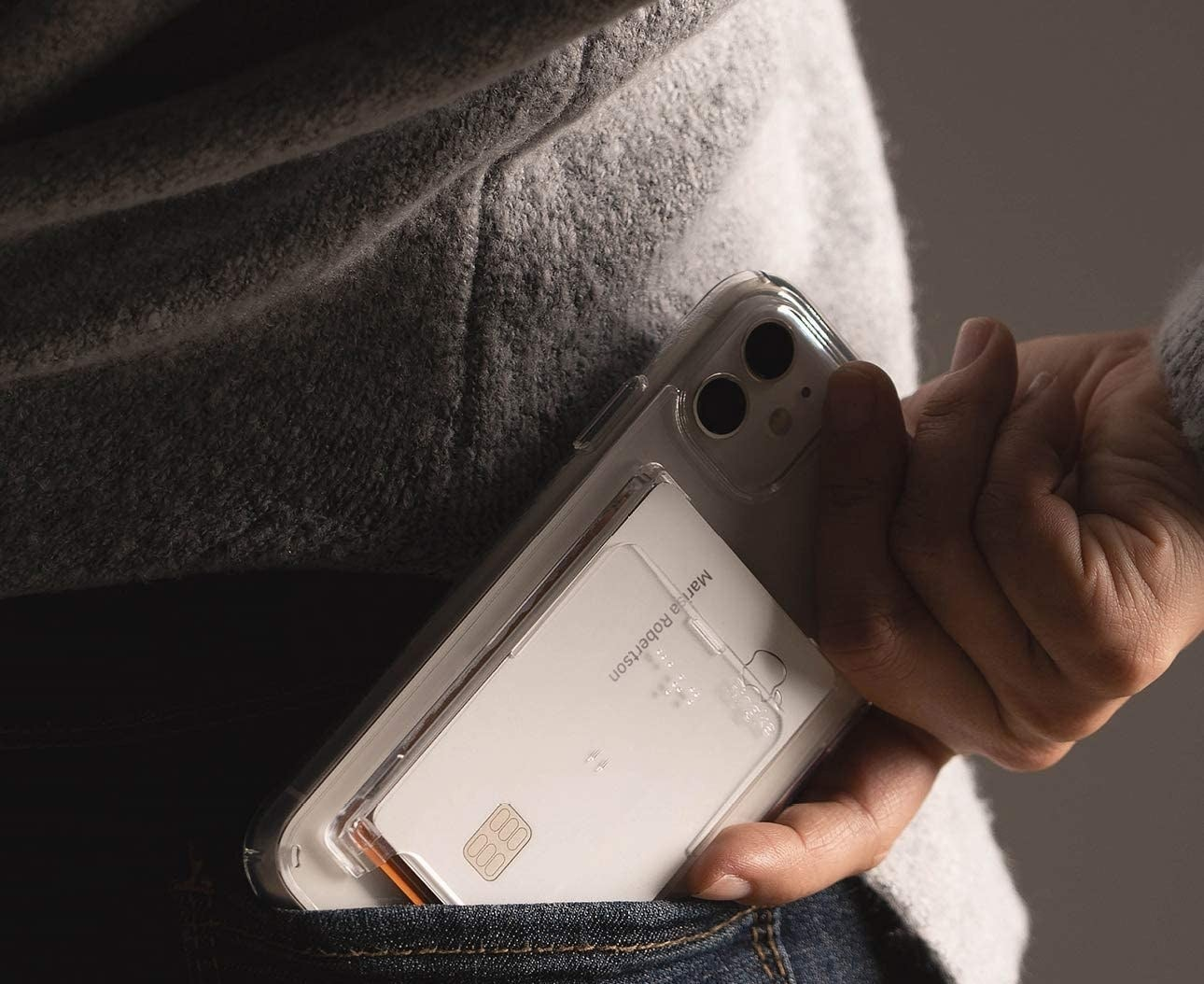 A person sliding their phone with the card slot into their back pocket