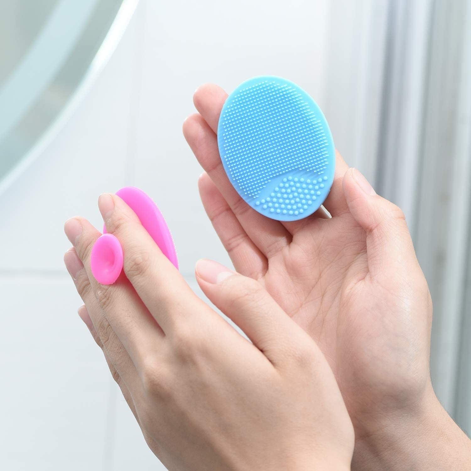 A person holding two face scrub pads
