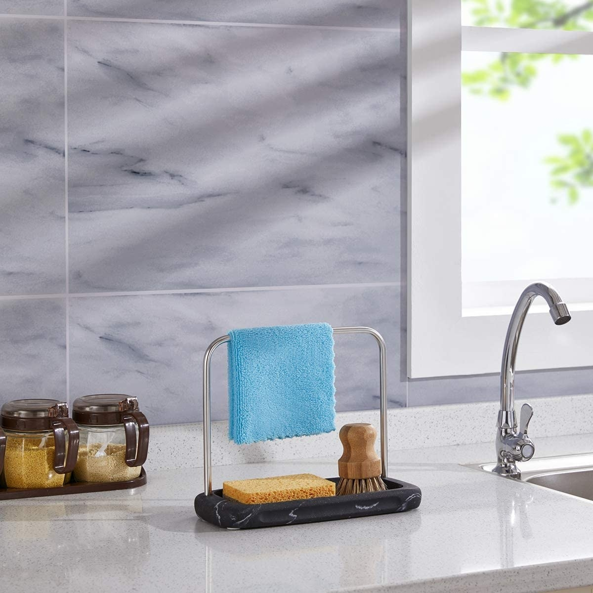 The caddy with a cloth hanging over it above a sponge and scrub on a counter