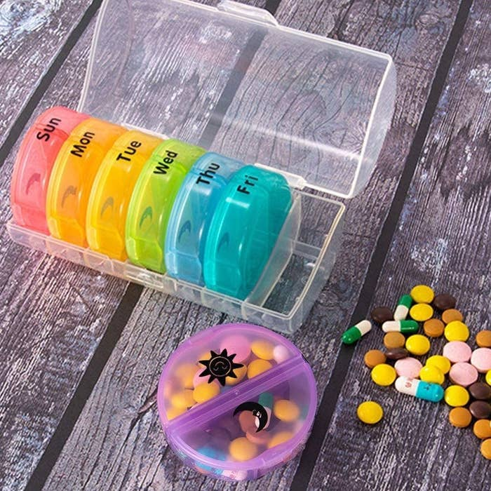 The weekly pill organizer with days of the week written on each container, as well as a sun and moon sticker to emphasize the divided sides of each container