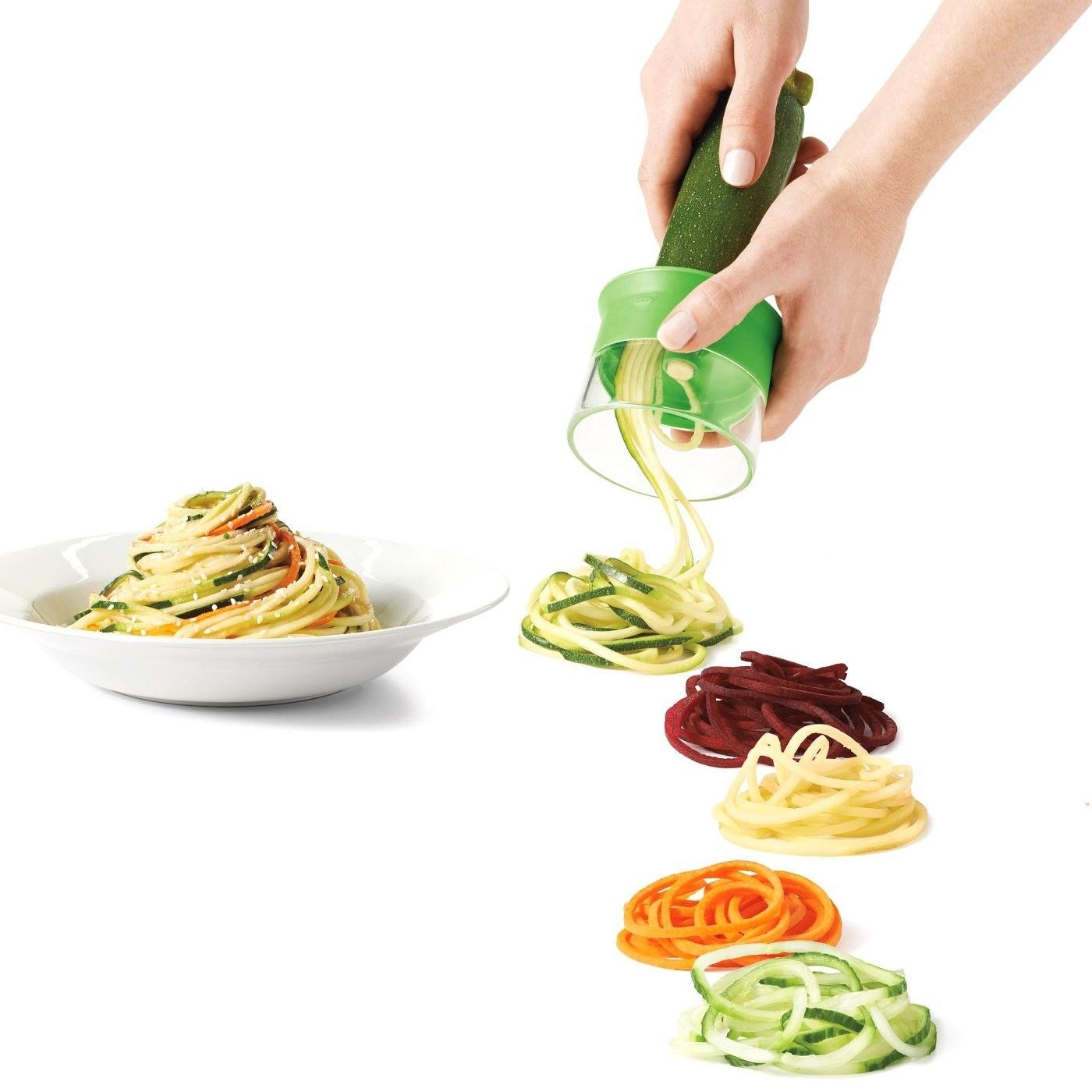 Hands using the spiralizer to make veggie noodles
