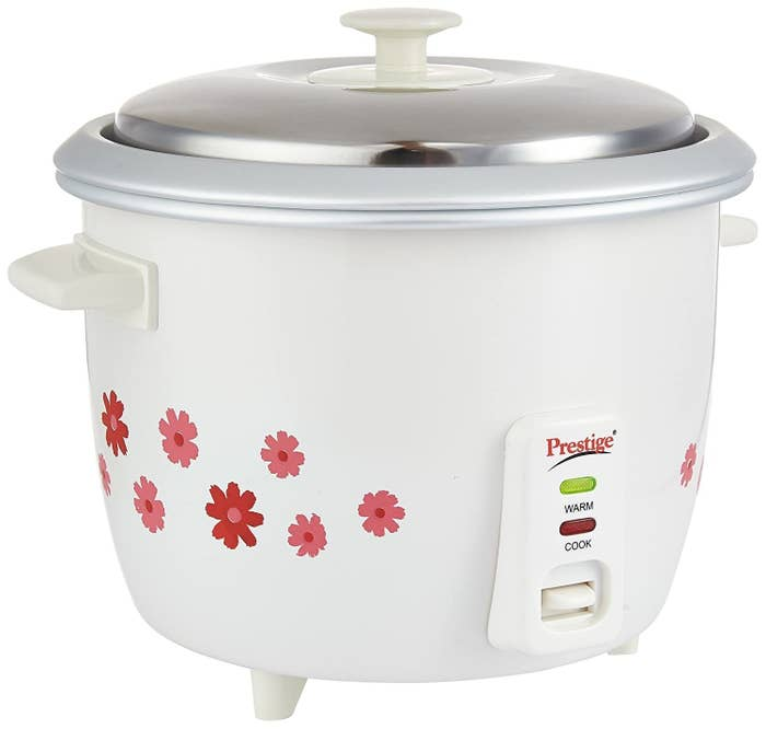 A white rice cooker with flowers printed on the side