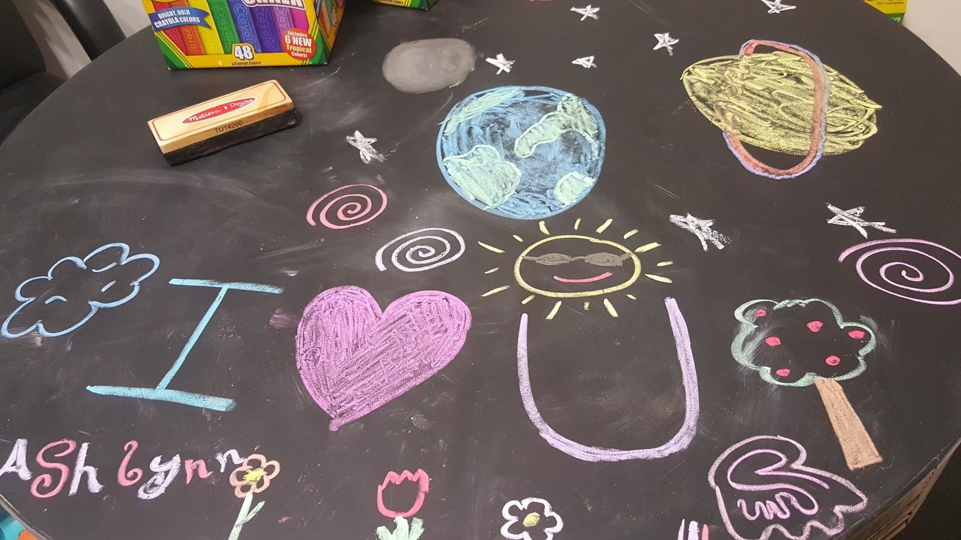 chalkboard table covered in chalk drawings