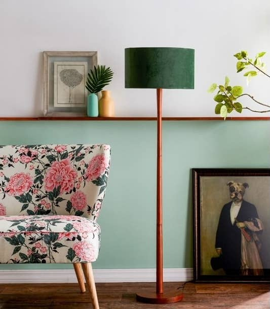 The lamp, which has a circular wooden base and wooden pole, both in a cherry wood finish, topped with a green velvet circular shade