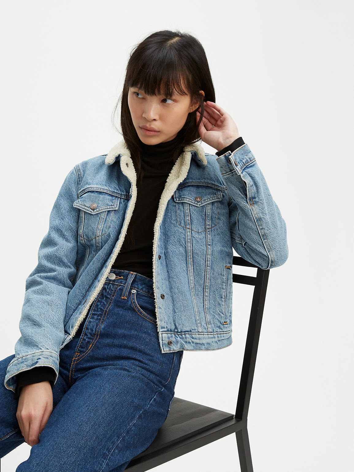 Model wearing denim jacket with press buttons
