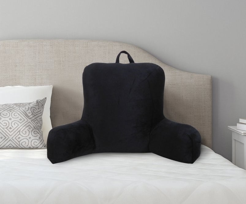 a black backrest pillow with a handle at the top resting on a bed