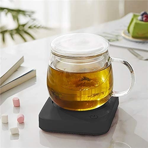 A cup of tea sitting on the mug warmer