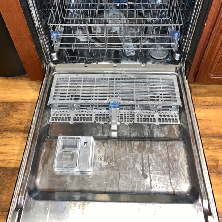 reviewer photo showing gunk and hard water built up on the inside of dishwasher
