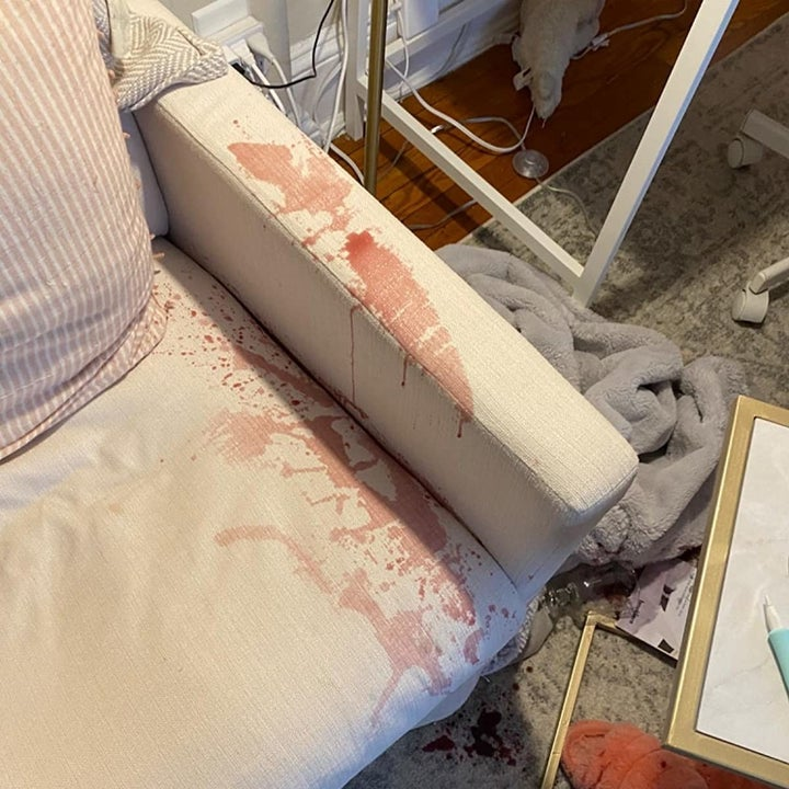 reviewer photo showing red wine stain on the arm of their white chair