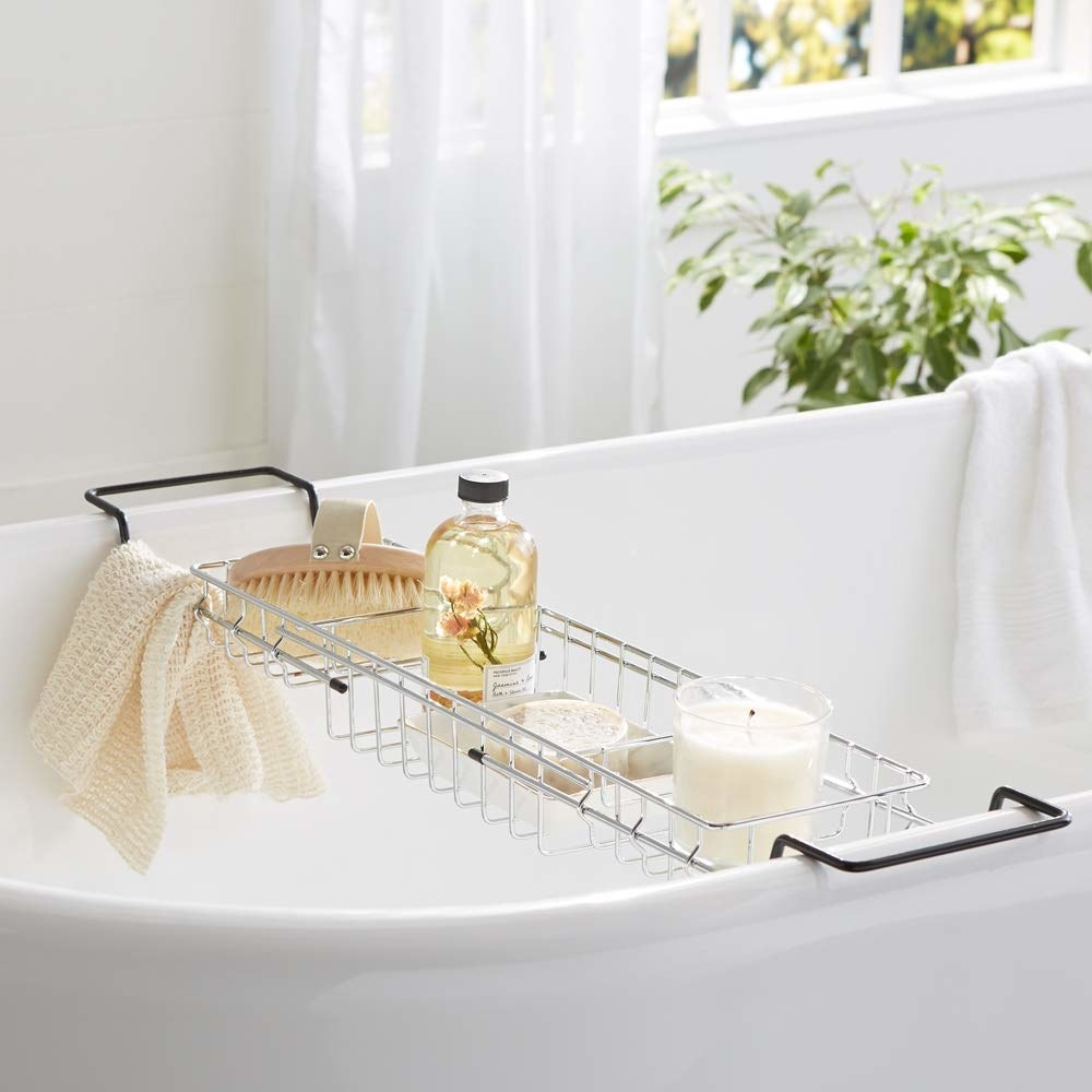 The bathtub caddy pictured on a bathtub with candles and other accessories on it.
