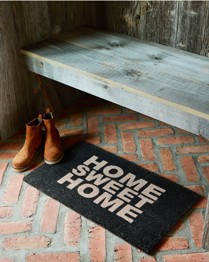 A door mat that says home sweet home on a brick path