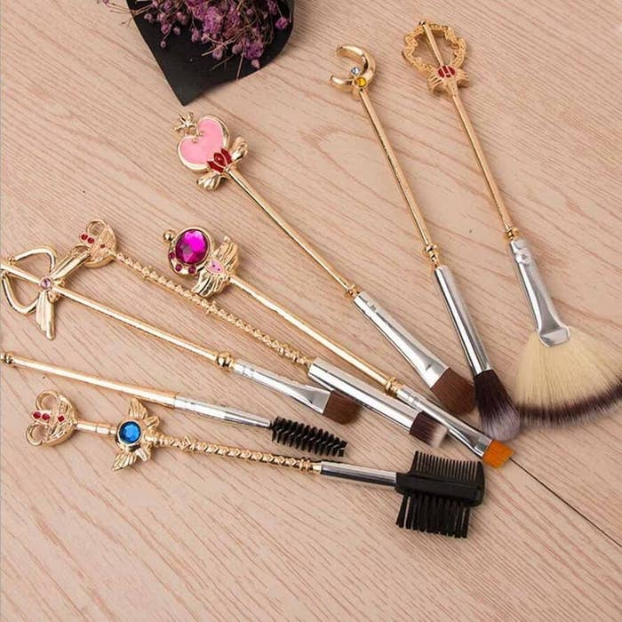 A bunch of small makeup brushes on a wooden table