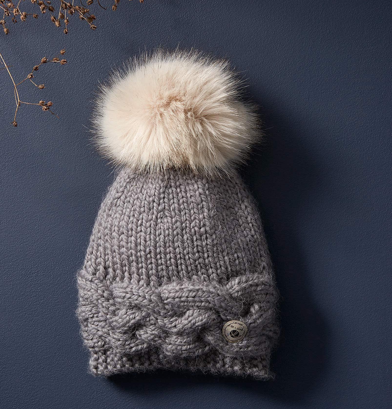 A knit hat with a pom pom on top lying on a plain background