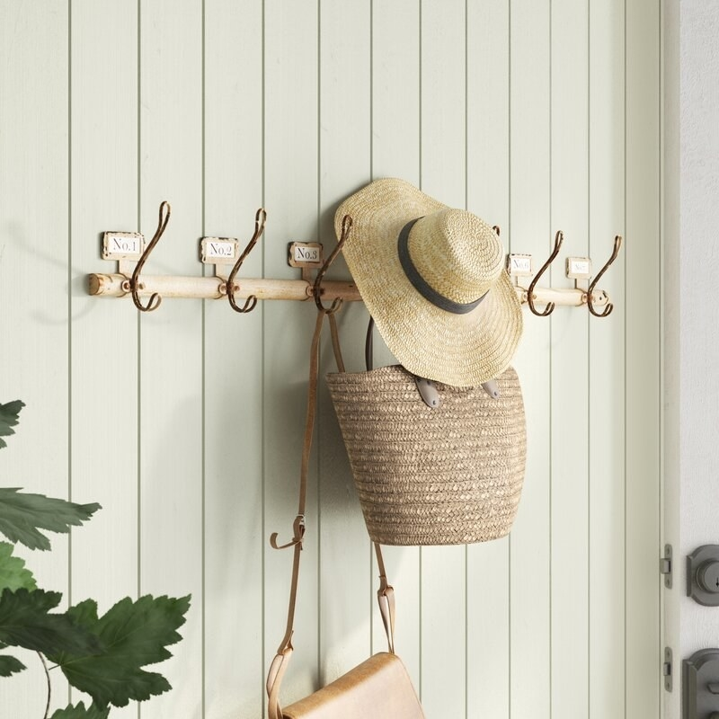 the white beachcrest home cashel mounted coat rack on a wall with two bags hanging from it