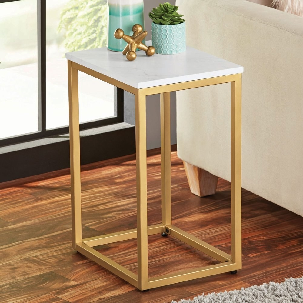 an end table with a white surface and gold legs in a room