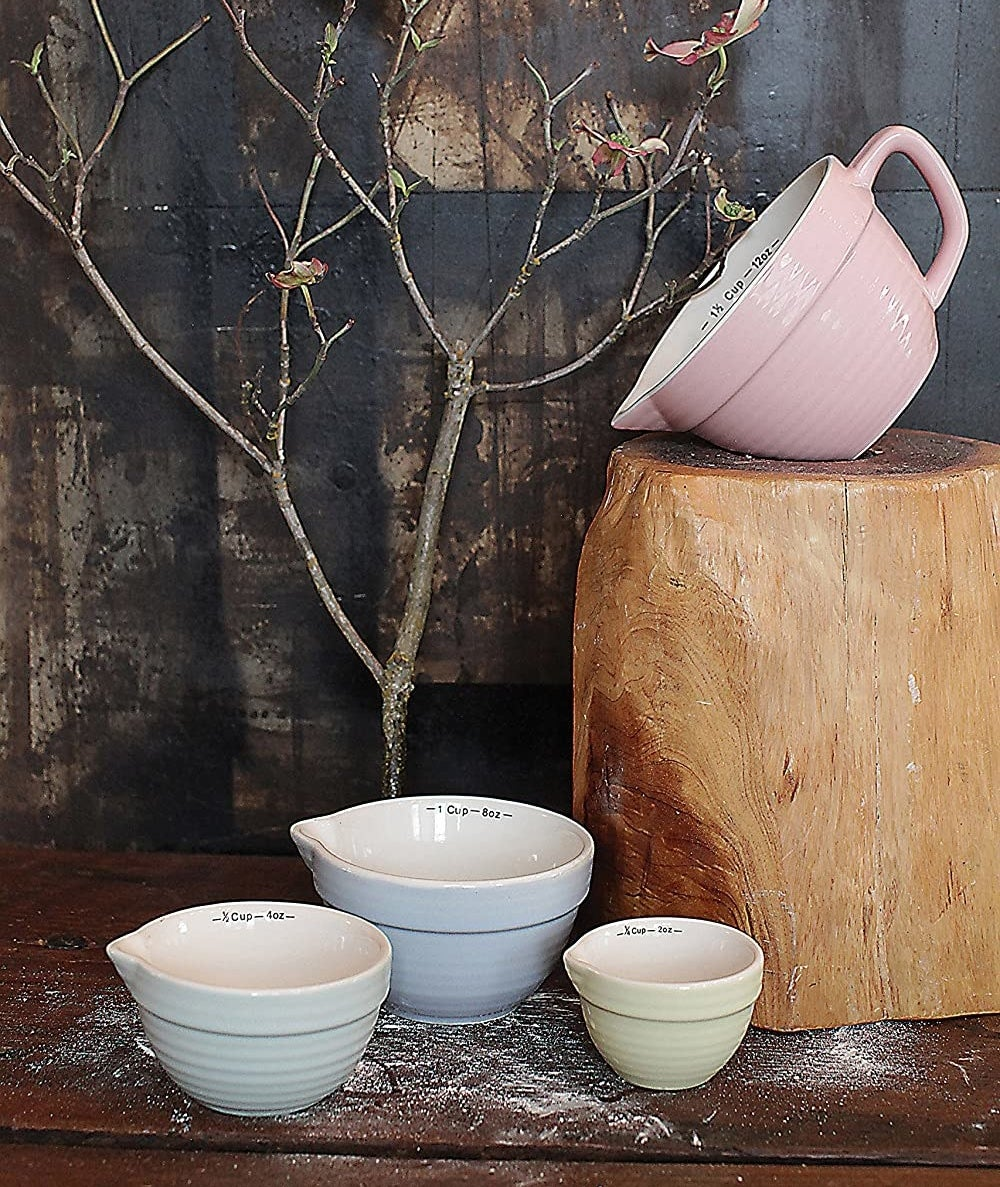 A set of four ceramic measuring cups staged in a rustic kitchen