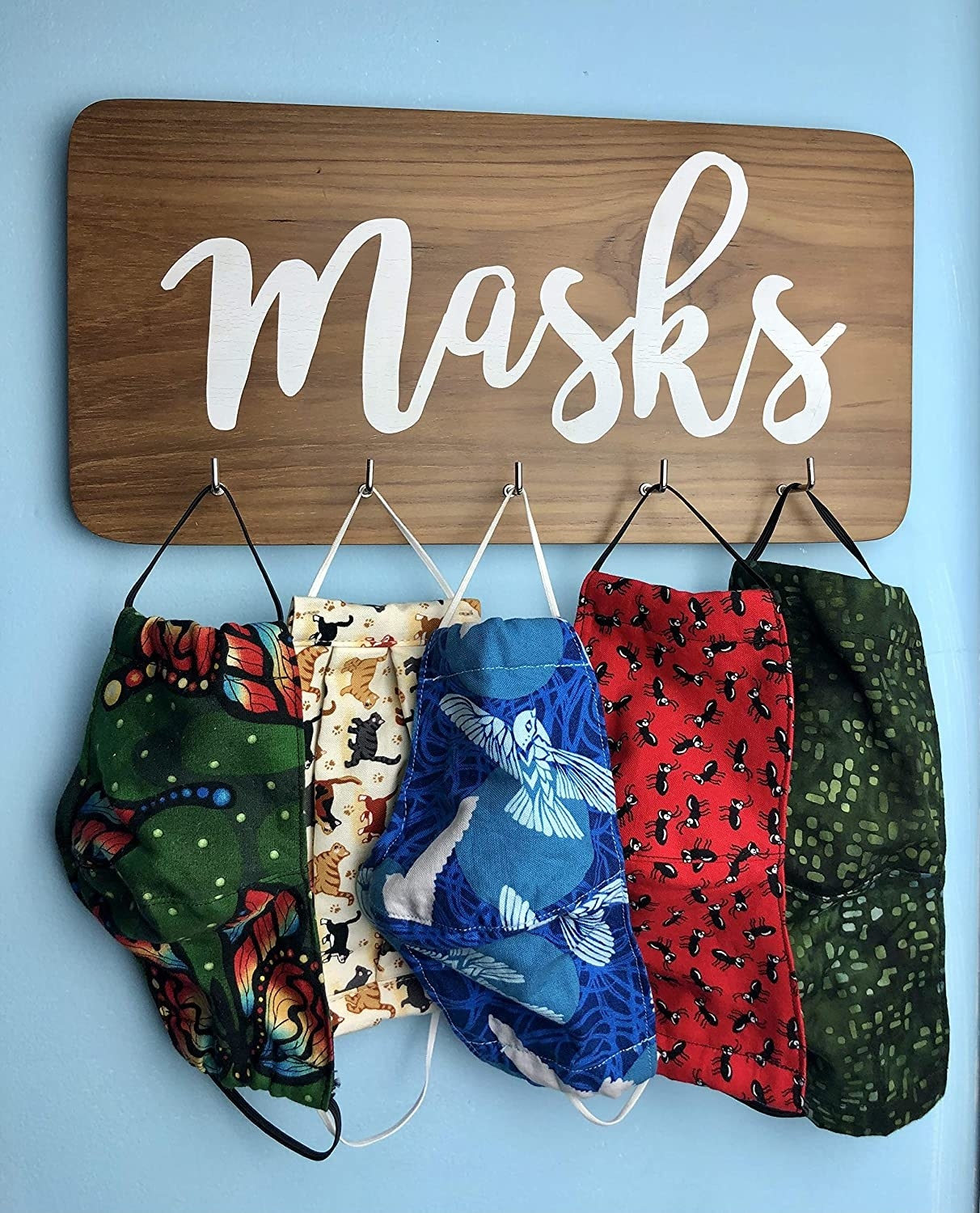 the face mask wall mounted rack with a mask hanging from each of its five hooks