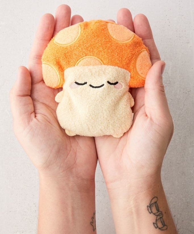Mushroom shaped heating pad inside a person's palms