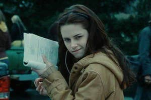 Bella holding up a book that she's reading to signal that she's busy