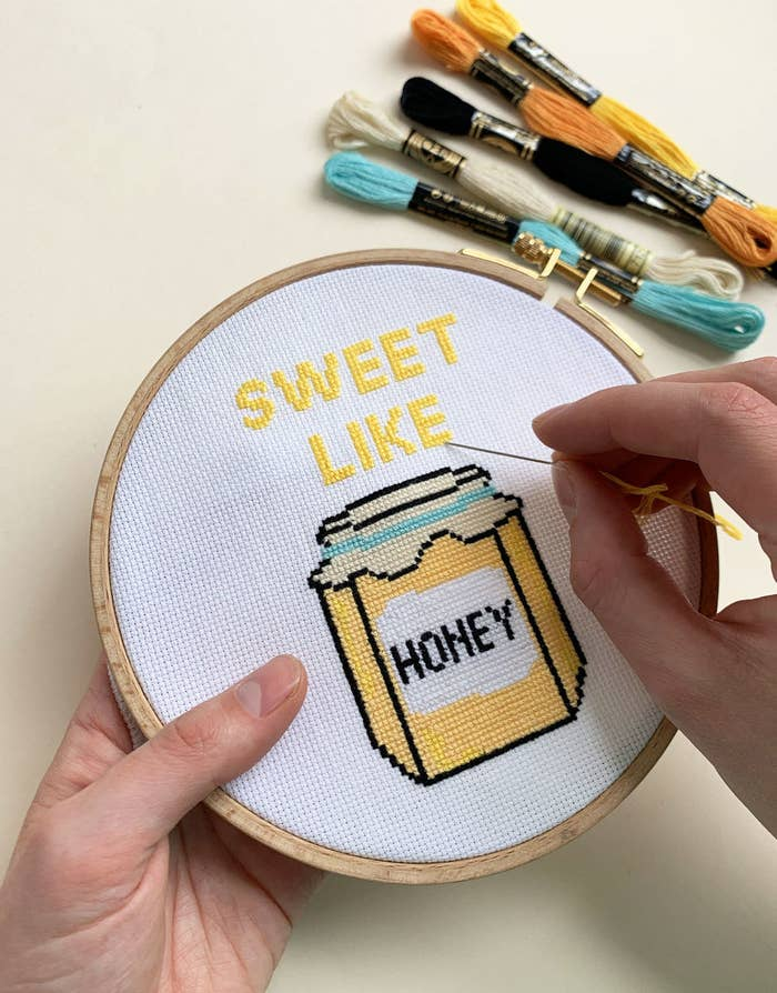 """Hands hold colorful cross stitch circle that says """"Sweet Like Honey""""  with a jar of honey design"""