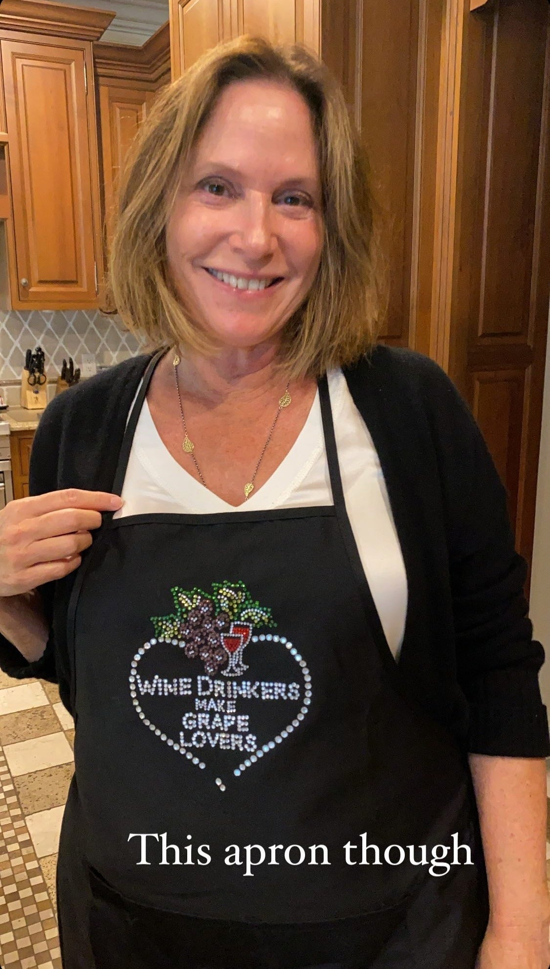 My mom in the kitchen wearing a funny and suggestive apron.