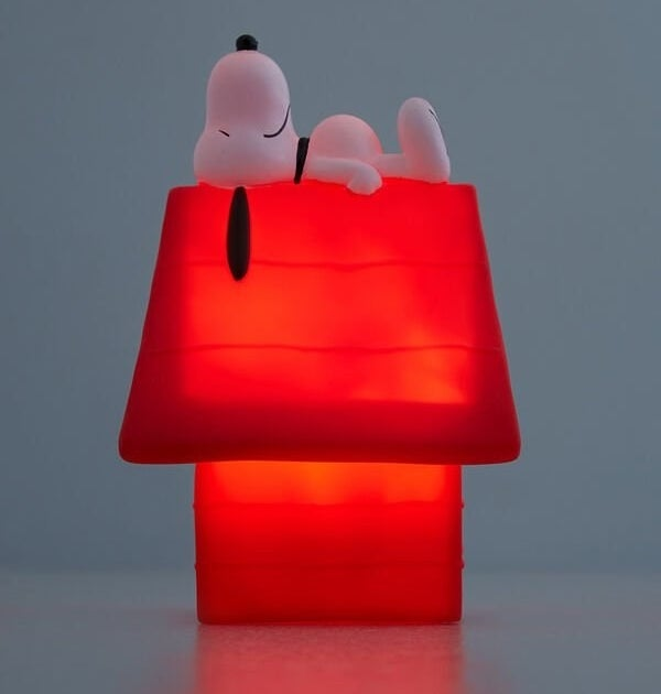 A night light in the shape of a small dog house with a small Snoopy dog lying on top