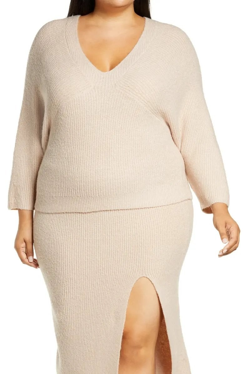Model wearing beige sweater and skirt