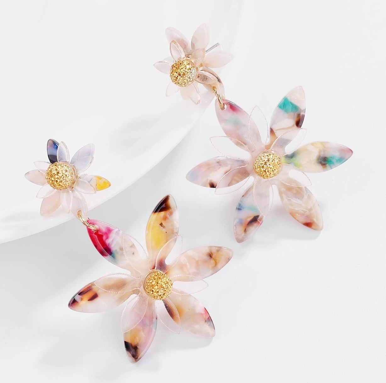 The multicolored drop earrings, each with a small and large flower with a gold center