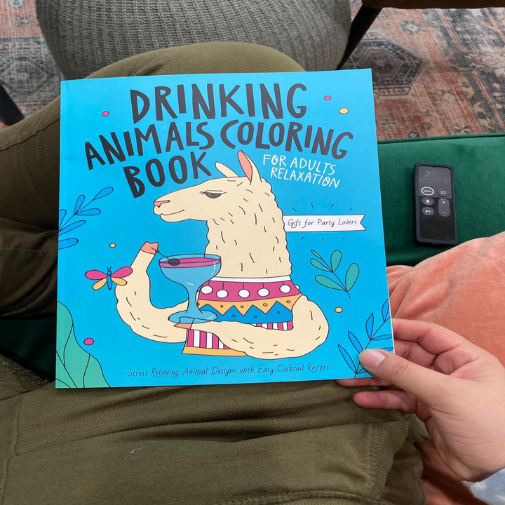 """Reviewer holds colorful book that says """"Drinking Animals Coloring Book"""" while sitting on a couch"""