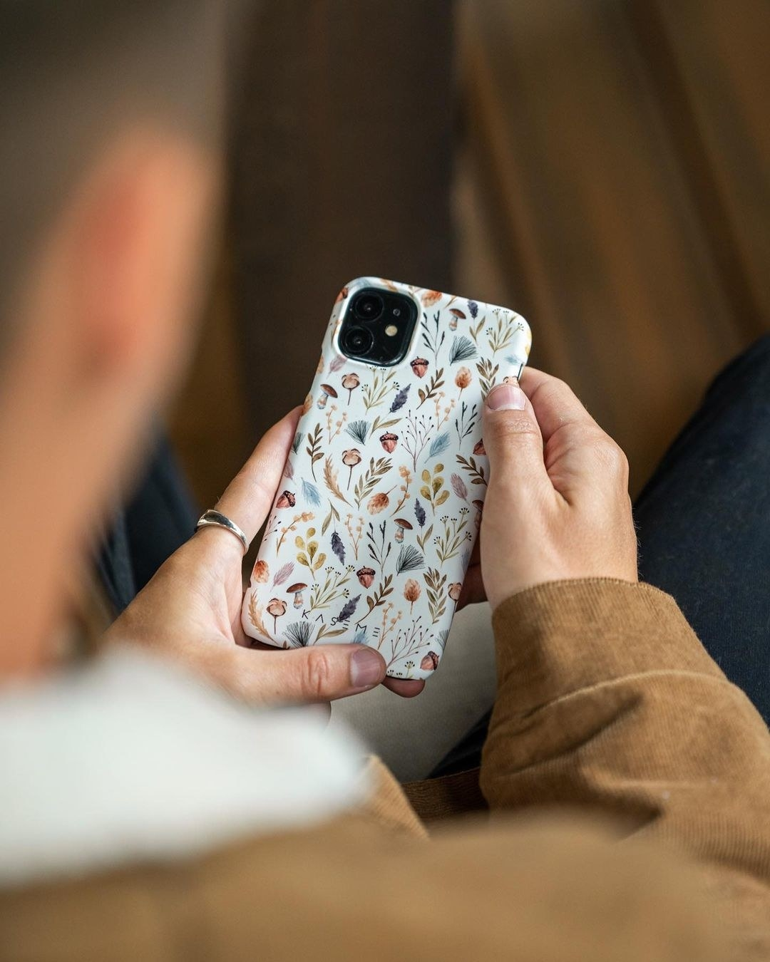 A person holding up their phone with a case on it