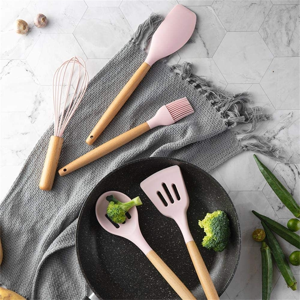 Five cooking tools in a pan and on a blanket next to the pan