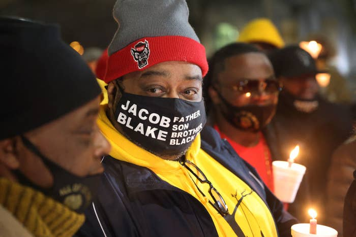 "Jacob Blake's father holds a candle and wears a face mask that reads ""Jacob Blake, father, son, brother, black"""