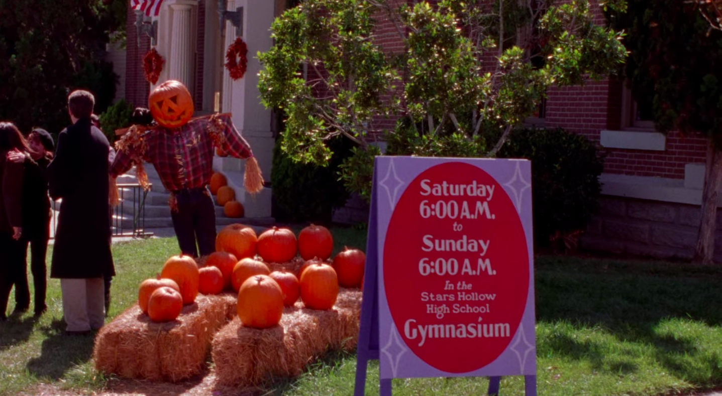 """A sign in Stars Hollow that says, """"Saturday 6 AM to Sunday 6 AM in the Stars Hollow High School gymnasium"""""""