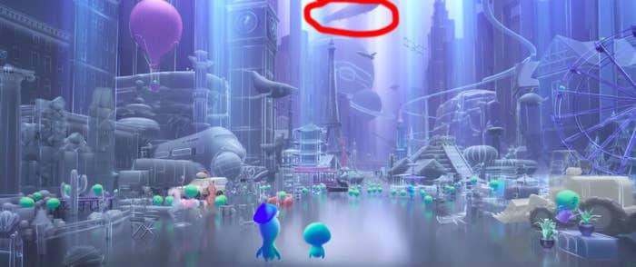 blimp floating in sky behind buildings